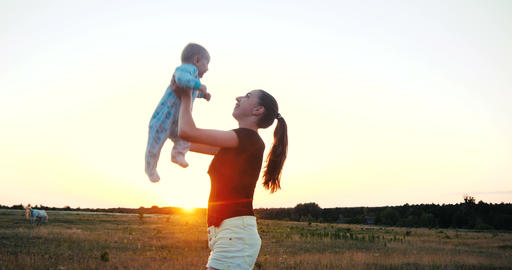 Emotional young woman raising her baby in hands in a field at sunset in slo-mo Footage