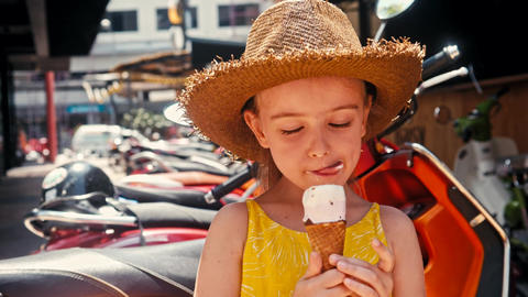 Little girl in straw hat eating ice-cream outdoors Street. Summer portrait GIF
