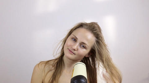Woman dries wet hair with a hair dryer Live Action
