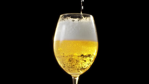 Golden foamy beer is poured slowly to the glass, beer glass in dark background Live Action