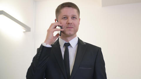 Executive businessman using smartphone for mobile conversation in office Live Action