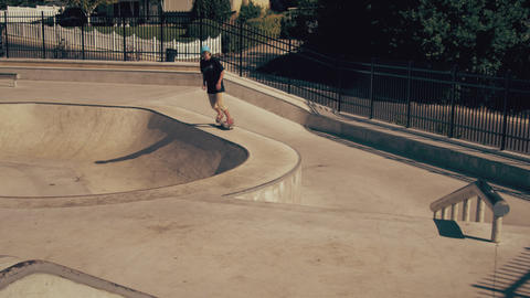 Shot of skater rolling up to an obstacle, jumping it, and rolling away Footage