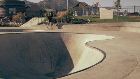 Panning shot of skater doing a backside 180 off a ladge Footage