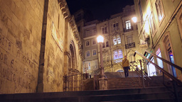 People walking down staircase at night in old portuguese city Coimbra Footage