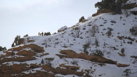 Static shot of group of people in winterclothes on top of cliff Footage