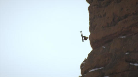 Slow motion shot of base jumper skiing down a hill then doing three back flips i Footage