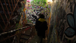 People Walking Down Staircase With Graffiti In Monster Kabinett Berlin Germany stock footage