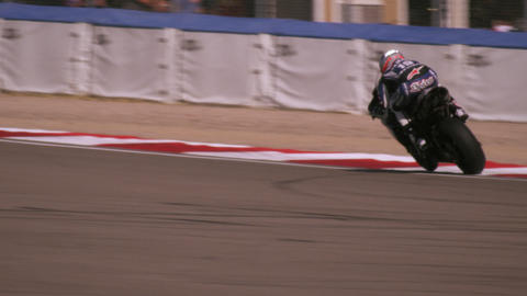Slow motion shot of motorcycle racer turning a curve and coming very close to th Footage