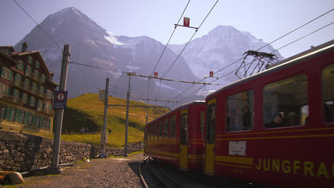Swiss railcar full of passengers passes hotel Footage