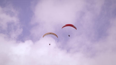 Long distance shot of two paragliders soaring side by side in Switzerland Live Action