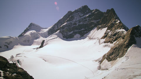 Panning lens flare shot of a Swiss mountain peak Footage