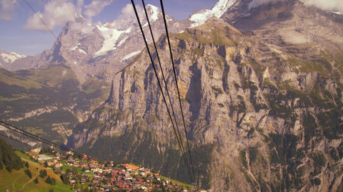 Tracking aerial shot of a village at the foot of the Swiss alps Footage