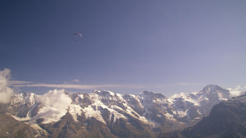 Long distance shot of a paraglider hovering above the Swiss alps Footage