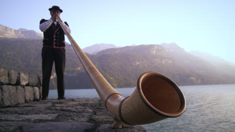 Low-angle footage of man playing alphorn next to lake Footage