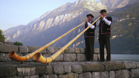 Two alphorn players perform at lake's edge Footage