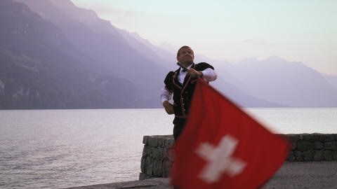 Man artfully twirls and tosses Swiss flag Footage