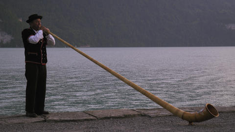 Man plays alphorn while standing next to lake Footage