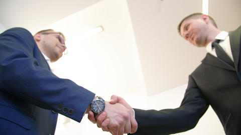Two business man shaking hands while meeting in business office, white Live Action