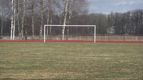 Empty early spring province stadium and football field with gates, zoom out Footage