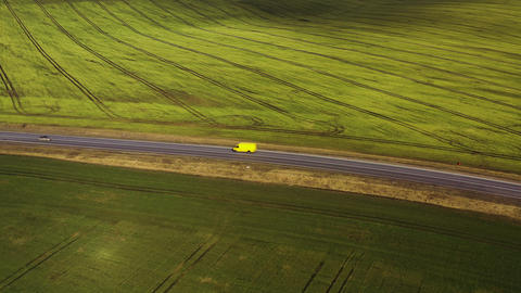 Top view of a cars driving along a rural road between two fields Archivo