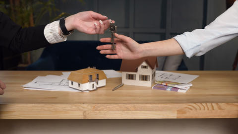 Close up shot of female realtor hands giving key to female clients Footage