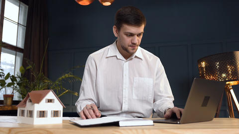 Young male architect working on the new desing of house using 3d house model Live Action