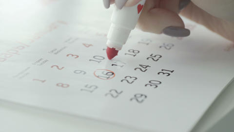 Woman hand circle day on paper calendar. 17st day of the month Live Action