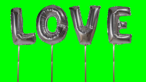 Word love from helium silver balloon letters floating on green screen ビデオ
