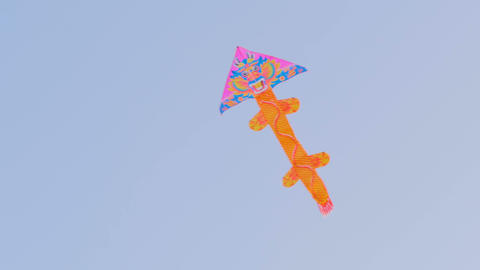 Colorful kite flying in blue sky GIF