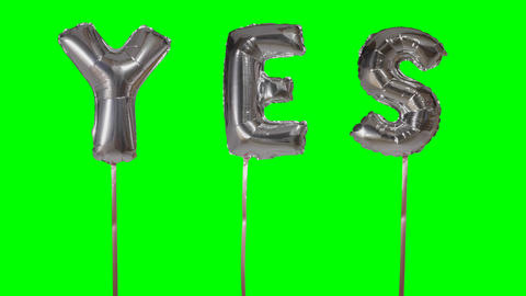 Word yes from helium silver balloon letters floating on green screen Live Action