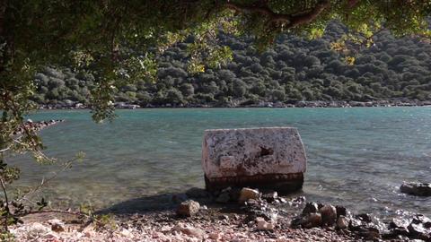 Broken ancient crypt stands in the water near sea shore in Kekova Archivo