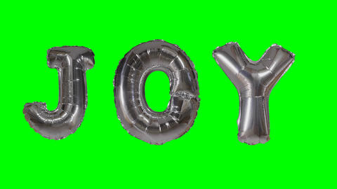 Word joy from helium silver balloon letters floating on green screen Footage