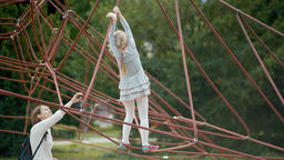 Blond Girl is Playing on Net Climber on the Playground with her Mother Archivo