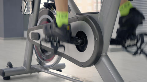 Woman legs spinning pedals on the spin bike Live Action