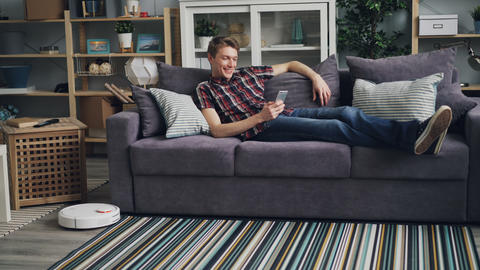 Smiling guy is sufring the Internet with smartphone relaxing on sofa while Footage