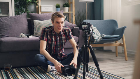 Emotional young man blogger is recording video about virtual reality glasses Live Action