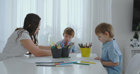Mom helps two sons to perform preschool homework to draw a pencil drawing Archivo