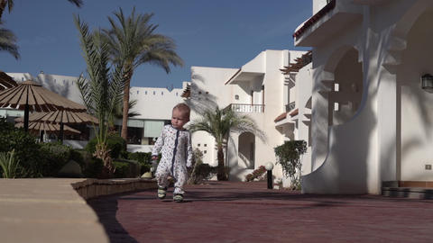 One year old baby walks along a tropical hotel in slow motion Footage