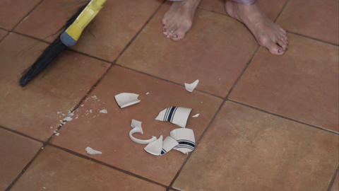 Barefoot woman cleaning up broken tea cup on floor Footage