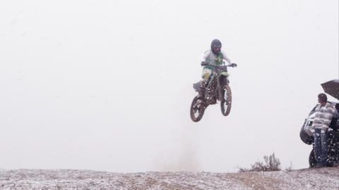 Motorcycle jumping over hill in the falling snow with spectators and a Toyota pi Footage
