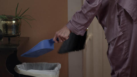 Woman in pajamas emptying dust pan into garbage Footage