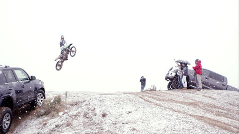 Motocycle jumping over hill between two SUVs and spectators Footage