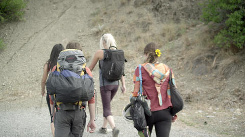 Shot following three women and a man hiking with climbing gear Footage