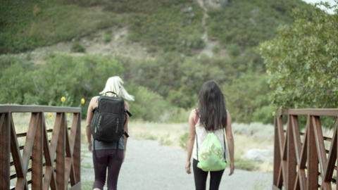 Two women hiking with backpacks accross a bridge Footage