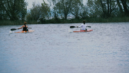 two girls athletes boating in canoes on lake Footage