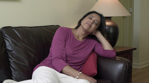 Woman sitting on couch watching TV Footage