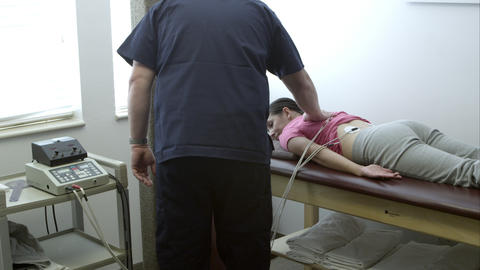 Therapist checking on woman's electro muscle therapy Footage