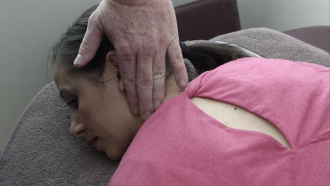Therapist examining woman's neck on table Live Action