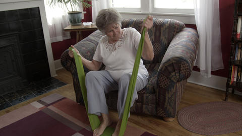 Elderly woman doing exercise with elastic bands at home Live Action