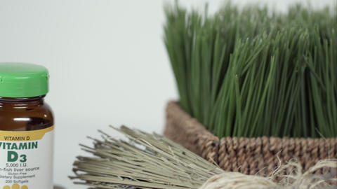 Panning shot of wheatgrass and vitamin bottle Footage